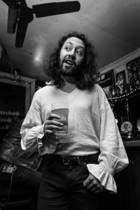 Man with long hair and beard in linden shirt with gathered flared cuffs holding pint of beer in pub bar, Shakespeare's Head Brighton UK. Black and white nightlife documentary photography. © P. Maton 2017 eyeteeth.net