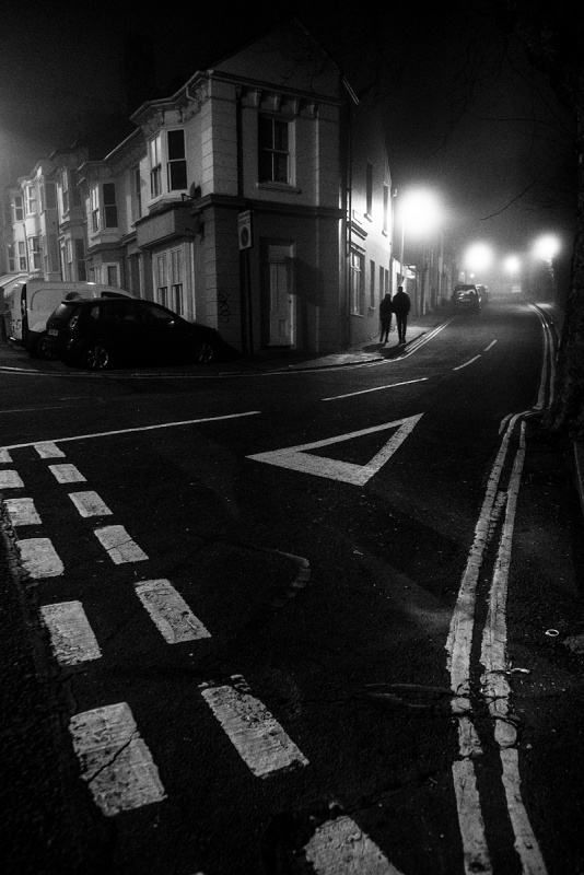 Couple walking up Howard Terrace  in fog silhouetted by lamp light with road junction markings in foreground. Urban night photography black and white. Brighton UK. ©P. Maton 2017 eyeteeth.net