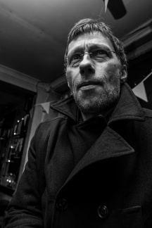 Man in wool overcoat with spectacles speaking in bar. Shakespeare's Head Pub Brighton UK. Black and white urban nightlife photography. © P. Maton 2017 eyeteeth.net