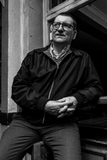Man in Harington jacket leaning on ledge in front of pub window torso length portrait black and white nightlife photograph. Shakespeare's Head pub Brighton UK. © P. Maton 2017 eyeteeth.net