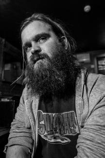 Young man with full beard in hoodie and Stingray tee shirt, black and white nightlife portrait Brighton UK © P. Maton 2017 eyeteeth.net