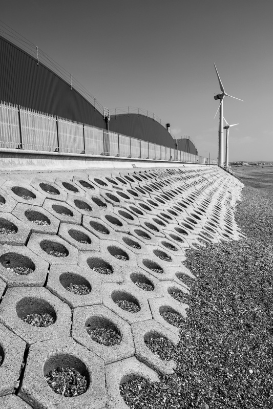 View East along Shoreham Harbour foreshore with wind turbines  in distance. Black and white Industrial landscape photography Sussex UK. Leading lines perspective.  P. Maton 2017 eyeteeth.net