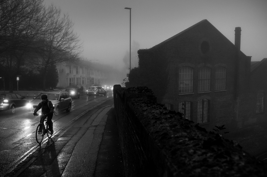Man cycling up hill in rain and fog with head light of car illuminating next to victorian industrial railway bridge and building. Chatham Place Brighton UK. Black and white urban winter night landscape street photograph © P. Maton 2017 eyeteeth.net