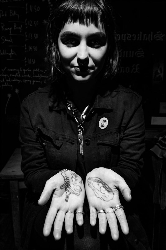 Young woman with black hair dressed in black with palms of hands turned up showing tattoos, black and white high contrast portrait alternative fashion