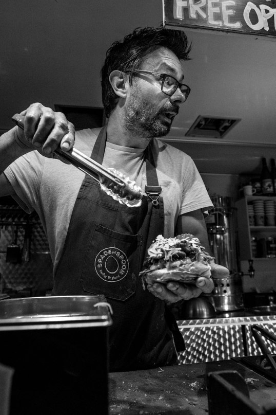 Spade an Spoon serving pulled pork at the Spiegle Tent Brighton UK, black and white social documentary portrait of man at work. ©P. Maton 2017 eyeteeth.net