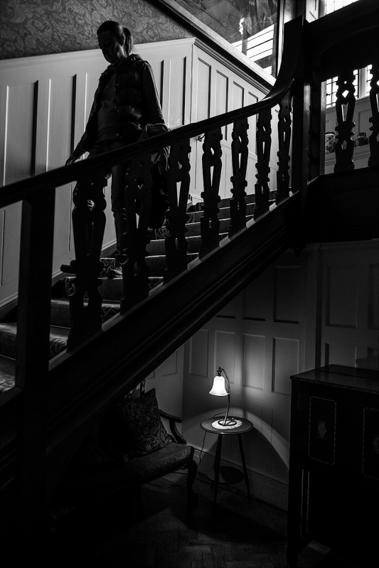 Woman walking down staircase with lamp below, Arts and Crafts movement interior, Standen East Sussex UK. Black and white documentary photography. © P. Maton 2017 eyeteeth.net