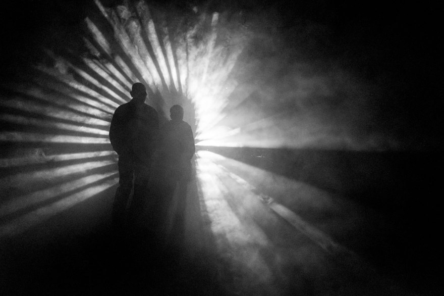 Silhouette of people waling into rays of light through smoke, For The Birds Brighton Festival UK Black and white landscape art instillation ©P. Maton 2017 eyeteeth.net
