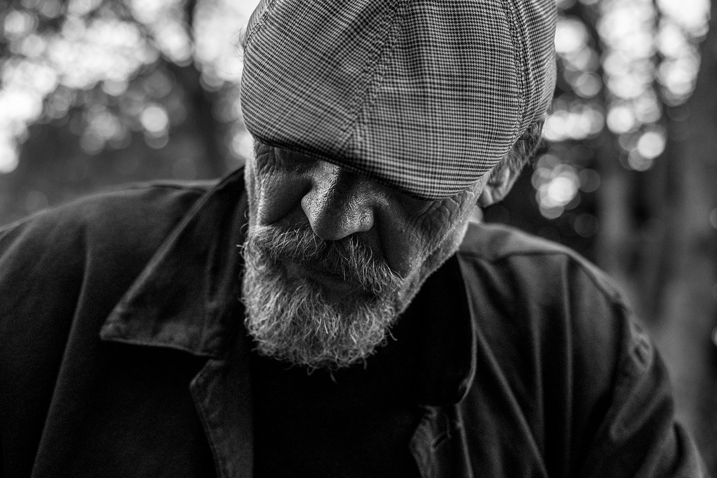 Senior man with beard in flat cap looking down with eyes hidden, Chatham Place Brighton UK black and white landscape character portrait © P. Maton 2017 eyeteeth.net