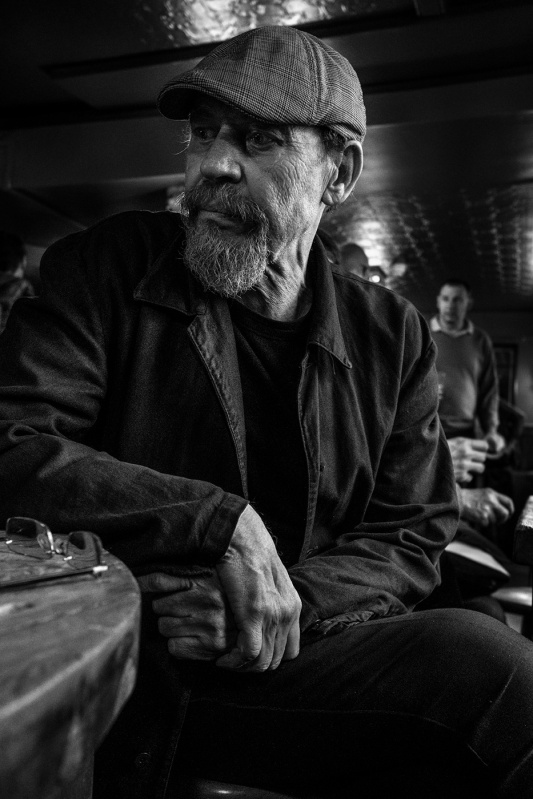 Bearded man wearing flat cap sitting at table in bar, Evening Star Pub Brighton UK. Black and white natural light documentary portrait. © P. Maton 2017 eyeteeth.net