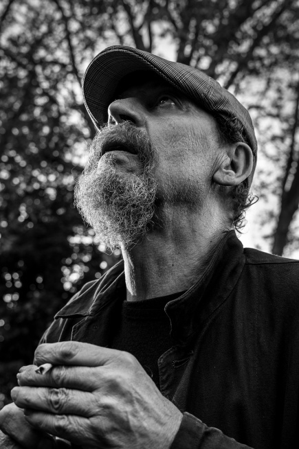 Bearded man wearing flat cap sitting outside holding a cigarette and gazing towards the sky, Shakespeare's Head Pub Brighton UK. Black and white natural light documentary portrait. © P. Maton 2017 eyeteeth.net