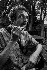 Man licking Rizla paper after rolling a cigarette Chatham Place Brighton UK black and white documentary portrait © P. Maton 2017 eyeteeth.net