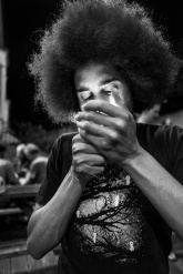 Man with afro hair style lighting cigarette with face illuminated by flame at night outside pub. Shakespeare's Head, Chatham Place Brighton UK black and white documentary portrait . © P. Maton 2017 eyeteeth.net
