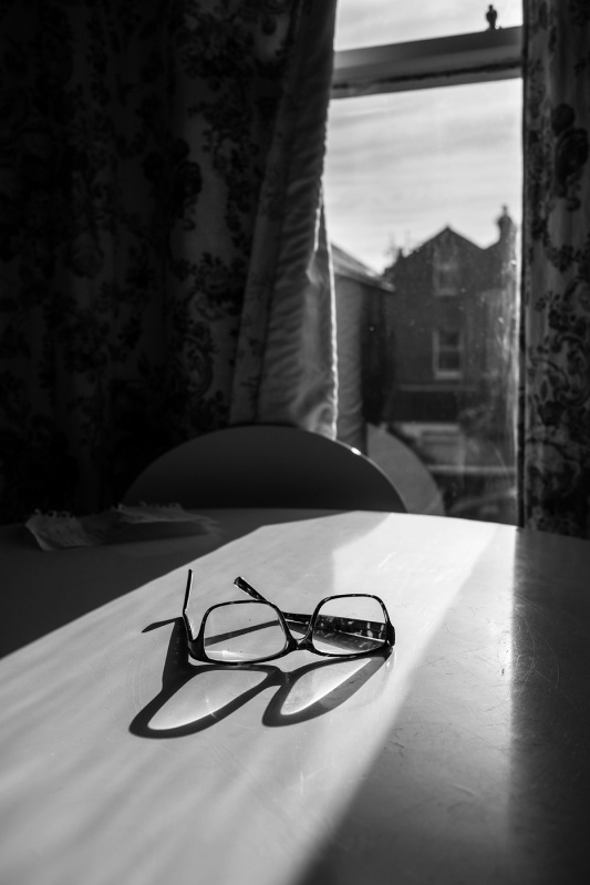 Spectacles casting shadow on on white table  illuminated through window black and white portrait urban documentary photograph ©P. Maton 2017 eyeteeth.net