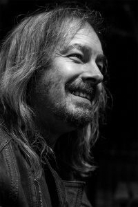Candid portrait of a man with long hair a scruffy beard and a gold tooth wearing a leather jacket, Brighton UK black and white photograph © P. Maton 2017 eyeteeth.net