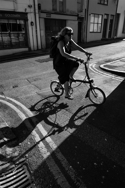 Woman cycling on fold up bicycle silhouetted by sunlight on corner of road, Trafalgar Lane Brighton UK black and white urban street photography ©P. Maton 2017 eyeteeth.net
