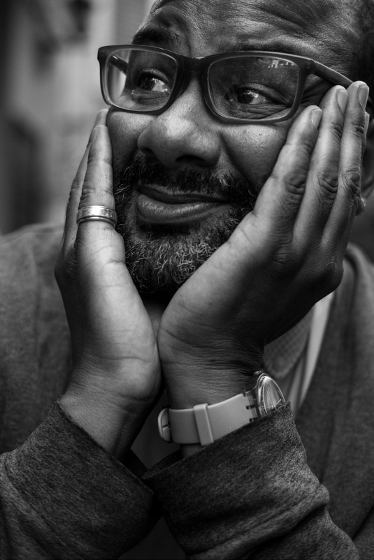 Man smiling with head in hands and spectacles, nightlife documentary portrait photography black and white portrait ©2017 P. Maton eyeteeth.net