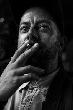 Man with beard and baseball cap raising cigarette to his lips black and white portrait face and hand Chatham Place Brighton UK © P. Maton 2017 eyeteeth.net