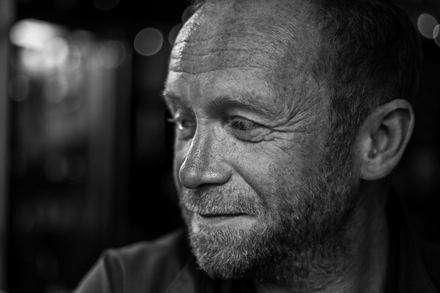 Man with freckles and short beard in bar looking to one side with bokeh in background, black and white portrait XT-2 Yashinon 50mm. Brighton UK © P. Maton 2017 eyeteeth.net