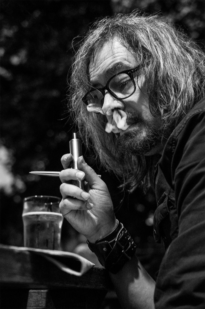Man with long hair and glasses vaping while doing crossword and drinking a pint at a pub, Shakespeare's Head Chatham Place Brighton UK. Black and white nightlife portrait ©P. Maton 2017 eyeteeth.net