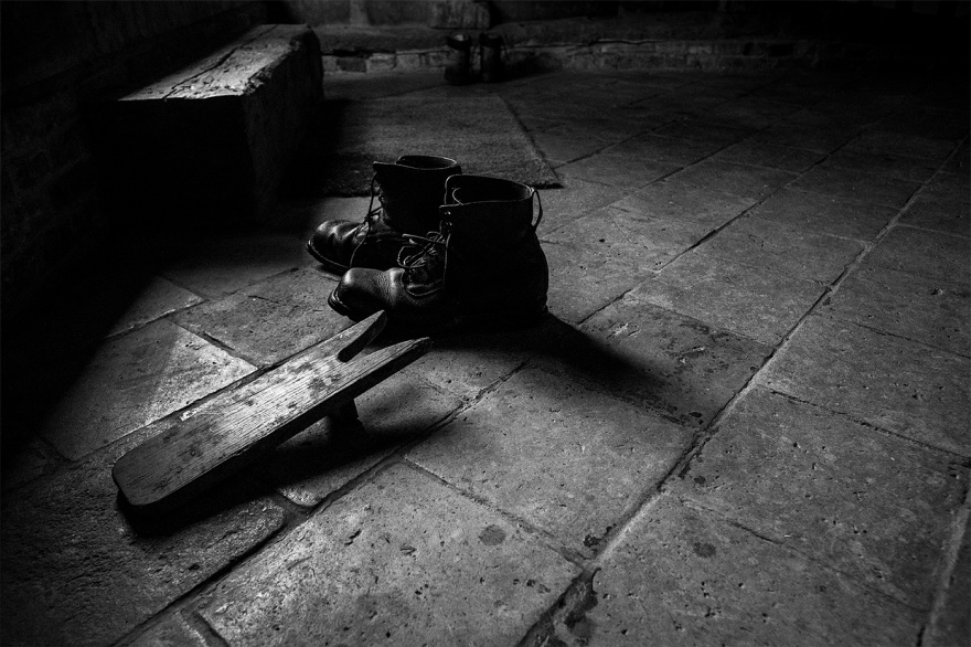 Old Swedish army boots with boot jack on flag stone floor in Tudor hall Purton Green Stansfield Suffolk black and white landscape © P. Maton 2017 eyeteeth.net
