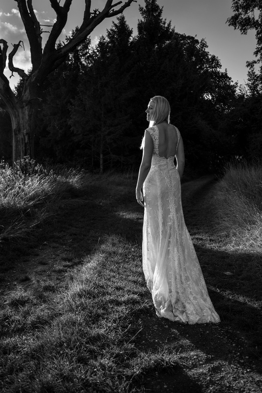 Woman in wedding dress walking away along path into woodland illuminated by evening sun turning head to light with face in profile, outdoor honeymoon shoot wit wedding dress black and white portrait Purton Green Suffolk © P. Maton 2017 eyeteeth.net