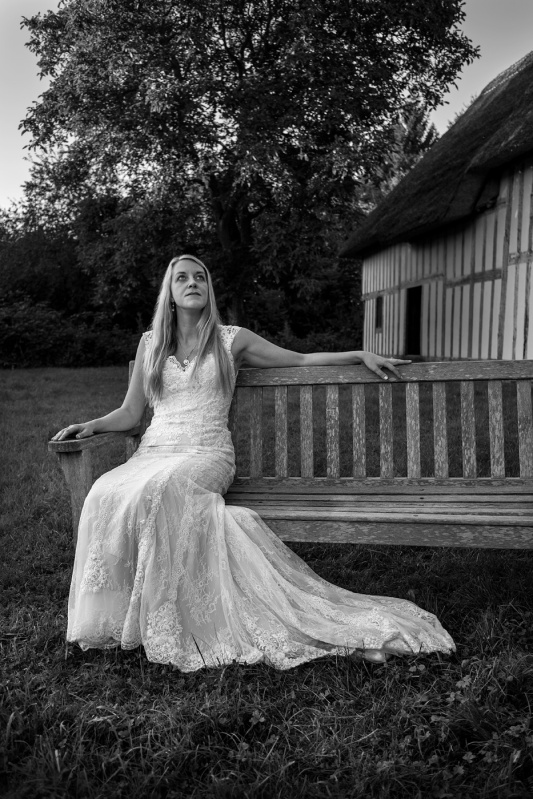 Woman in wedding dress sitting on wooden bench on lawn with Tudor hall in background, Purton Green Stansfield Suffolk black and white  portrait © P. Maton 2017 eyeteeth.net