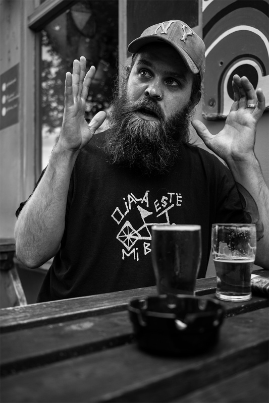 Man with large beard wearing a cap, sitting at table table with hands raised, black and white documentary portrait photography © P. Maton 2017 eyeteeth.net
