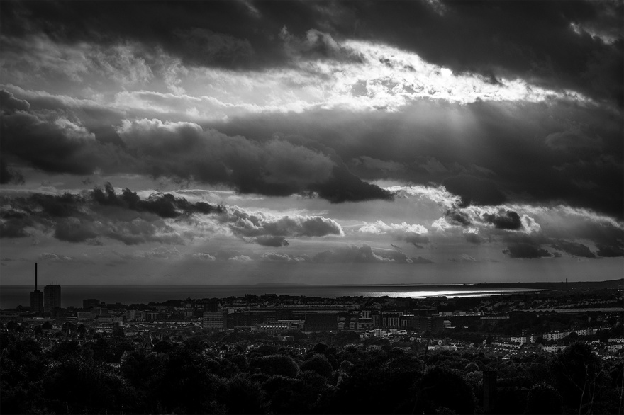 Sun light breaking through clouds over Brighton, view from Tenantry Down across city of Brighton UK to the sea and Isle of White, dramatic black and white landscape photograph. ©P. Maton 2017 eyeteeth.net