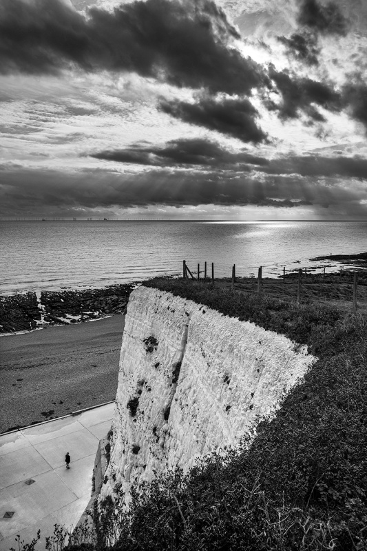 Dramatic clouds with breaking sunlight over sea, wind turbines, under cliff and chalk cliffs at Rottingdean East Sussex UK black and white landscape portrait © P. Maton 2017 eyeteeth.net