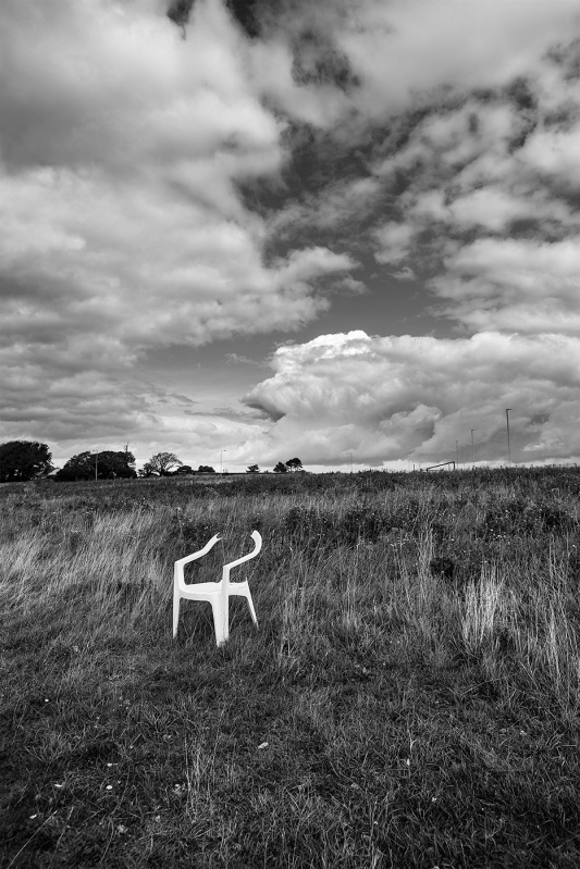 Broken plastic garden chair on grassland with dramatic clouds in background Tenantry Down Brighton Sussex UK black and white landscape portrait © P. Maton 2017 eyeteeth.net