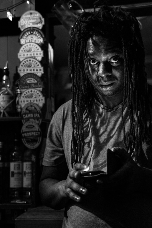 Man with dread locks lit by mobile phone looking at camera musician Charles Drayton at the Shakespeare's Head pub Brighton UK black and white portrait ©P. Maton 2017 eyeteeth.net