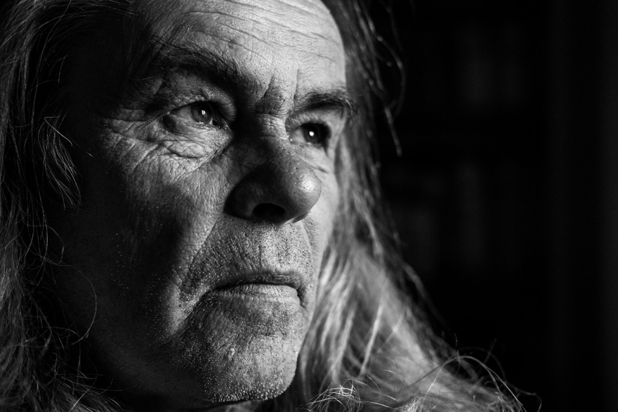 Portrait of a mature man with long hair looking into light wards right of frame, Oxfordshire UK black and white documentary landscape photograph ©P. Maton 2017 eyeteeth.net
