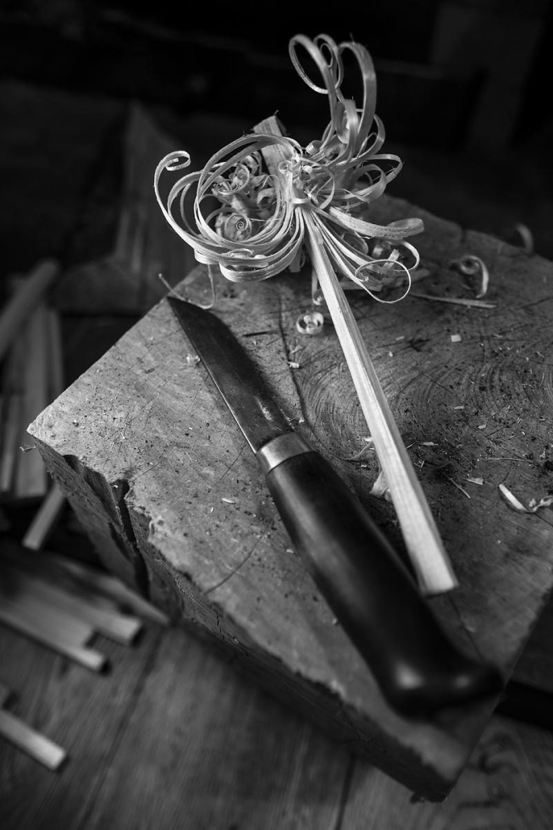 Finnish Puukko knife lying beside whittled feather stick on wooden block ©P. Maton 2017 eyeteeth.net