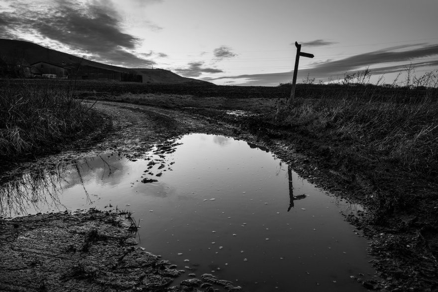 Footpath sign reflected in puddle on farm track Fulking West Sussex UK, black and white rural landscape © P. Maton 2018 eyeteeth.net