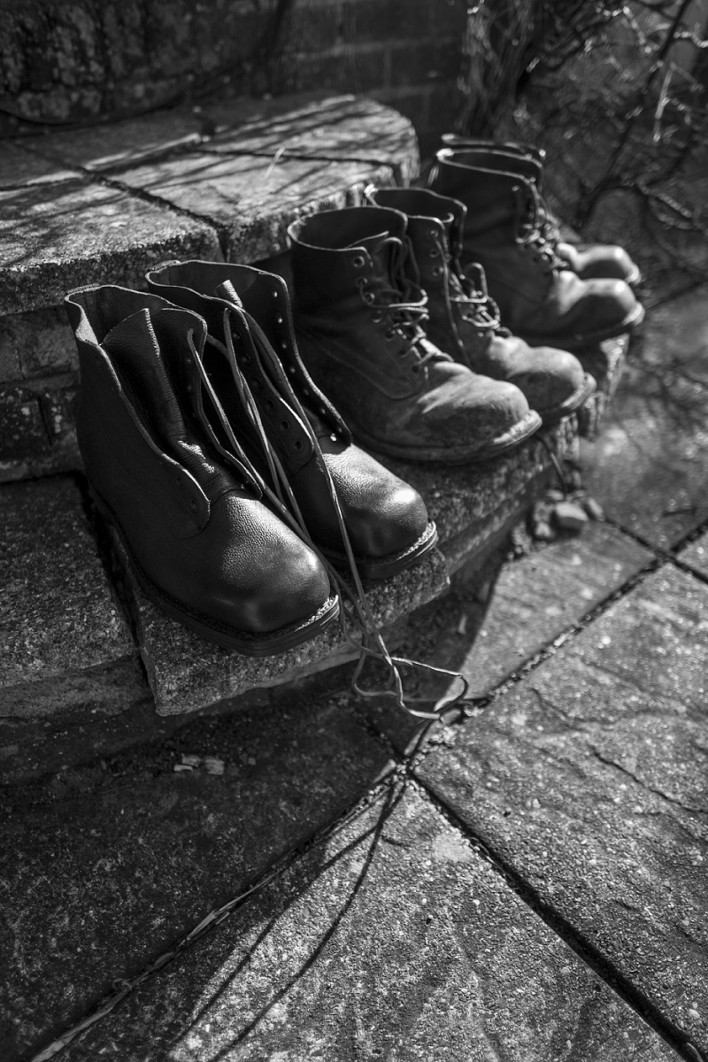 Three pairs of Treton Swedish army boots one brand new and tow older pairs sitting on stone steps, black and white documentary lifestyle photograph ©P. Maton 2018 eyeteeth.net