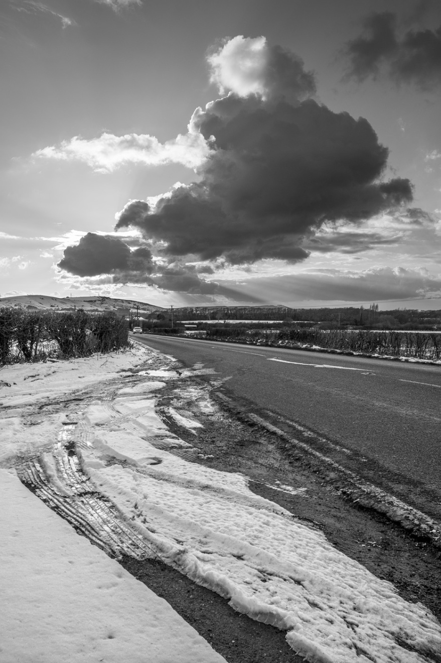 cloud obscuring sunset over the south downs with road and tyre marks in snow in foreground Newtimber West Sussex UK black and white landscape photograph © P. Maton 2018 eyeteeth.net