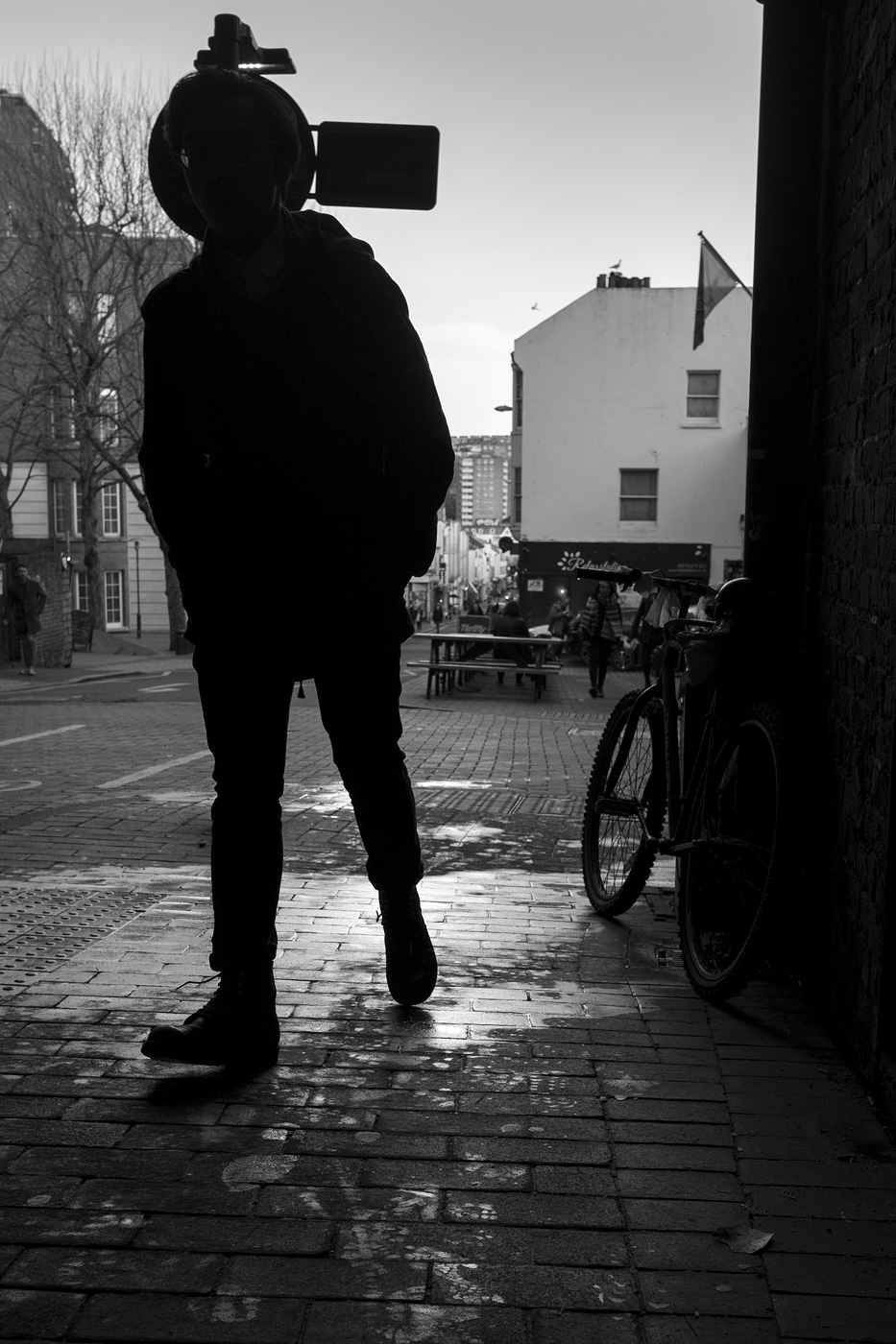 Silhouette of man walking into dark foreground with road sign obscuring head, Trafalgar Street North Laine Brighton UK black and white documentary street photography © P. Maton 2018 eyeteeth.net