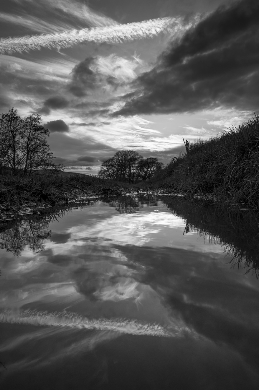 Dramatic clouds and contrail at sunset reflected in puddle, Mill Lane Poynings West Sussex UK black and white vertical portrait landscape rural countryside water photograph ©P. Maton 2018 eyeteeth.net