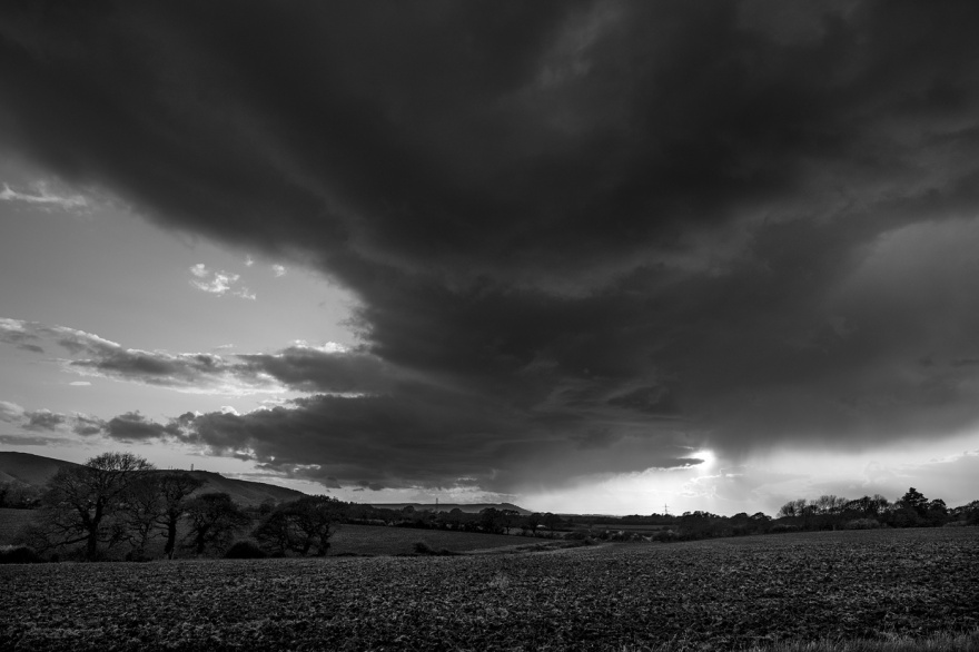 Sunset breaking through rain clouds by the South Downs with Chanctonbury Ring in distance, Poynings West Sussex UK black and white rural landscape  ©P. Maton 2018 eyeteeth.net