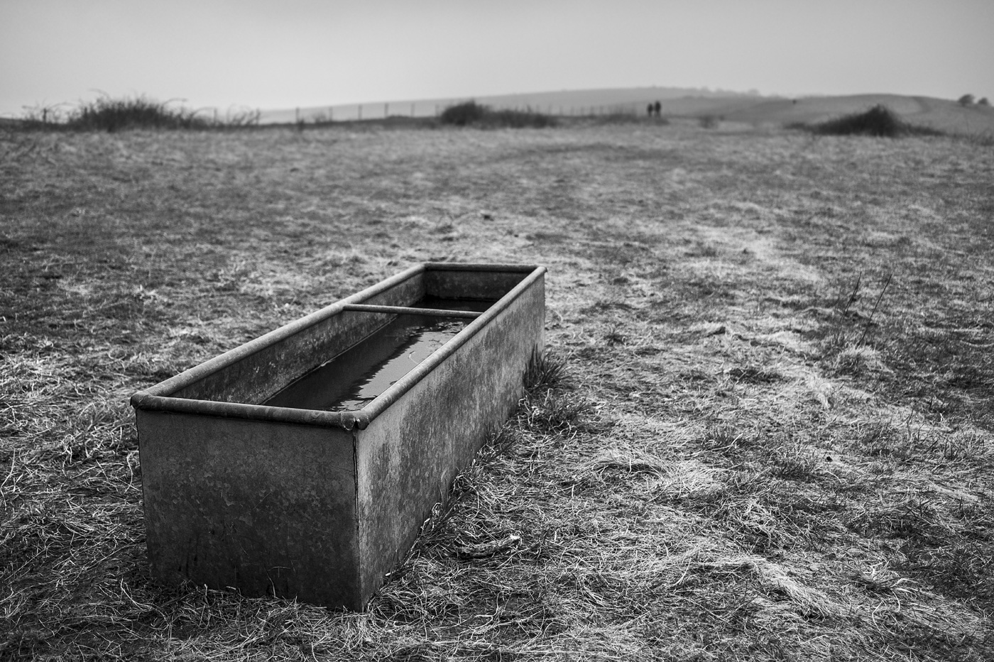 Distant people approaching water trough by the South Downs Way at Ditchling Beacon East Sussex UK overcast day black and white landscape photograph © P. Maton 2018 eyeteeth.net
