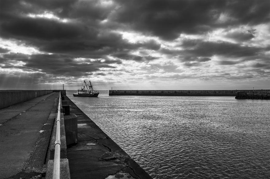 Trawler fishing boat entering the mouth of the River Adur by Shoreham Harbour West Sussex UK black and white nautical landscape with dramatic clouds ©P. Maton 2018 eyeteeth.net
