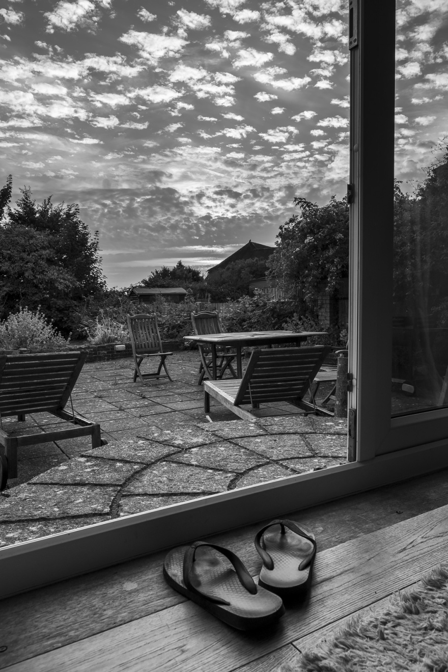 Evening sky with scattered clouds and evening sun with patio, french windows and flip-flops in foreground, black and white rural Britain garden scene ©P. Maton 2018 eyeteeth.net