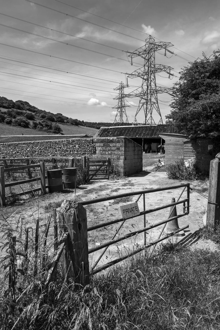 Metal gate with private sign leading to stable yard with electricity pylons in rural background, black and white rural British countryside landscape portrait, Mile Oak Farm West Sussex UK © P. Maton 2018 eyeteeth.net