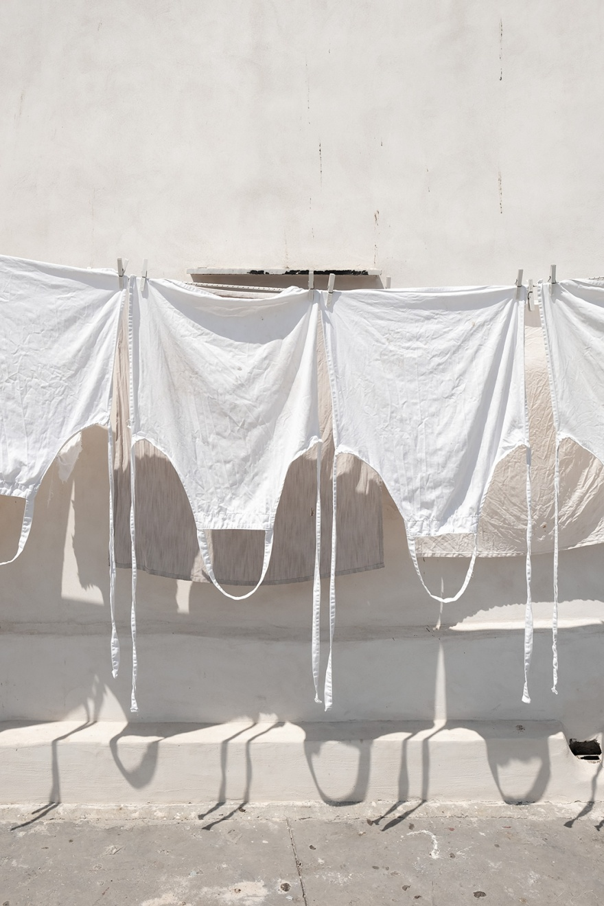 White aprons hanging out to dry in sunshine with whitewashed wall in background Via Marina di Corricella, Procida Italy abstract colour portrait composition urban street rustic photograph © P. Maton 2018 eyeteeth.net