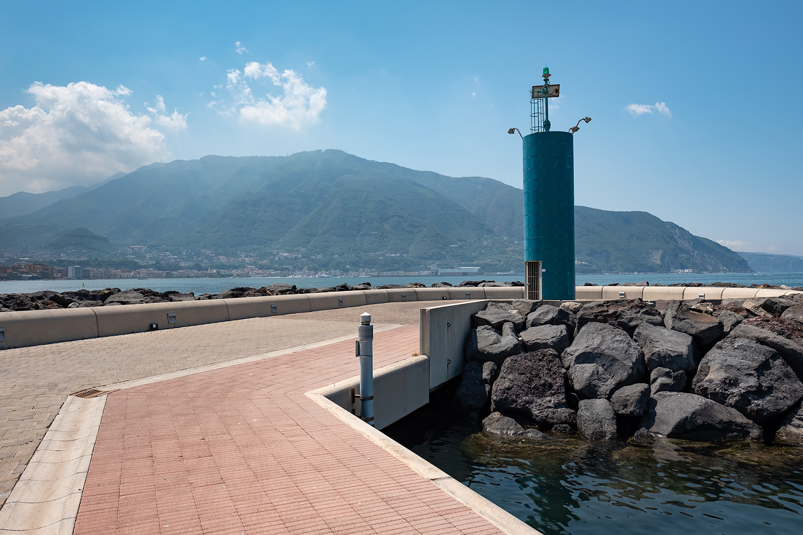 Beacon at entrance to Porto Marina di Stabia Italy with mountains in background, colour landscape photography ©P. Maton 2018 eyeteeth.net