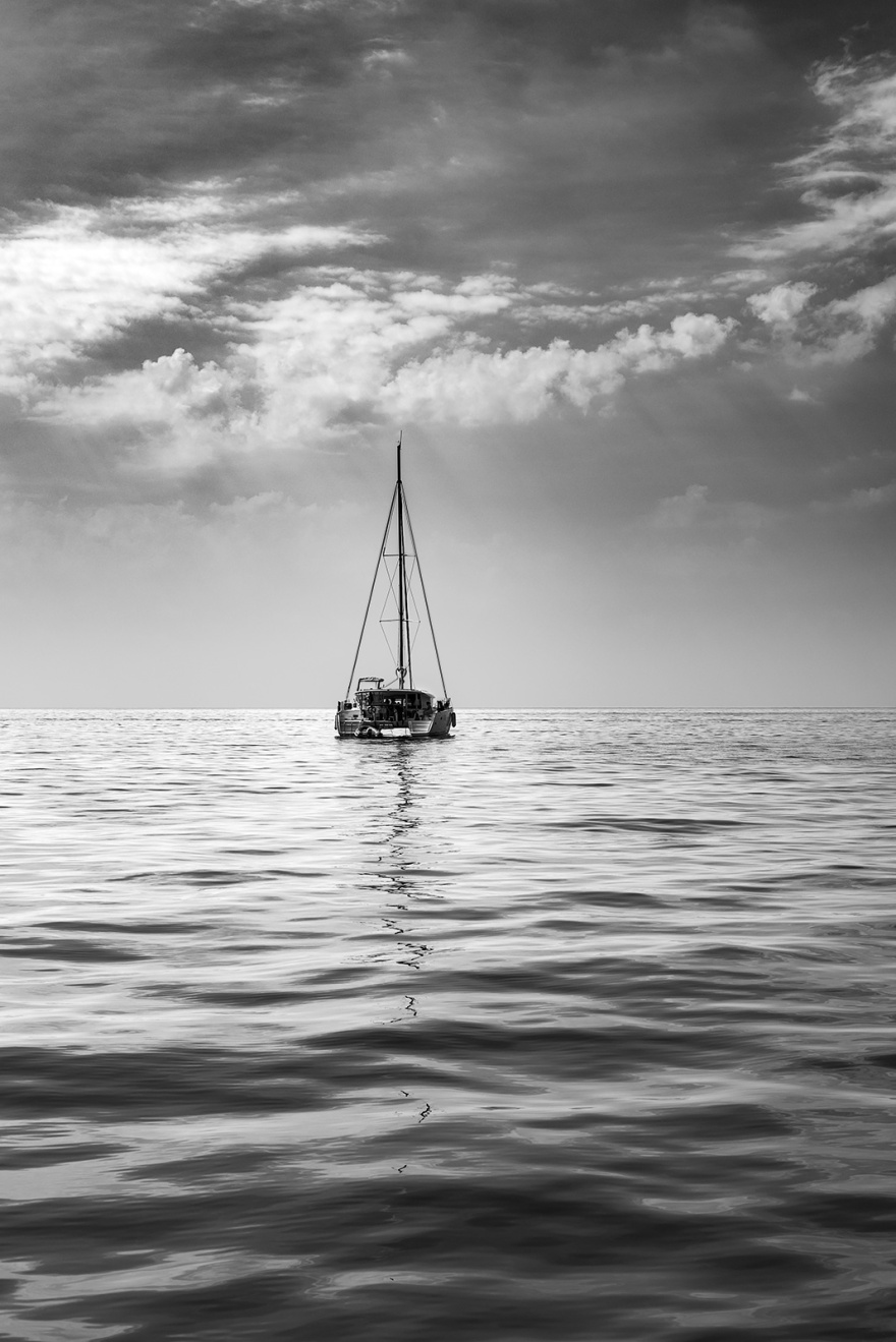 Catamaran afloat on calm glassy ocean with sails down  under light hazy clouds lit by sunlight off Isle of Ischia, Italy black and white monochrome vertical seascape photograph © P. Maton 2018 eyeteeth.net