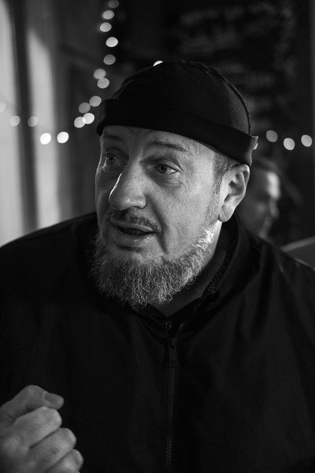 Man with beard wearing hat looking sideways in conversation candid black and white portrait Brighton UK © P. Maton 2018 eyeteeth.net