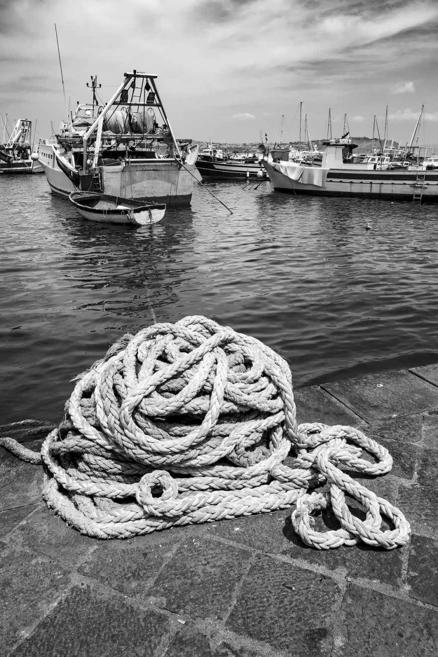 Rope piled on wharf with moored trawler fishing boat in background marina porto Procida, Isle of Procida, Italy Black and white Monochrome urban street portrait ©P. Maton 2018 eyeteeth.net