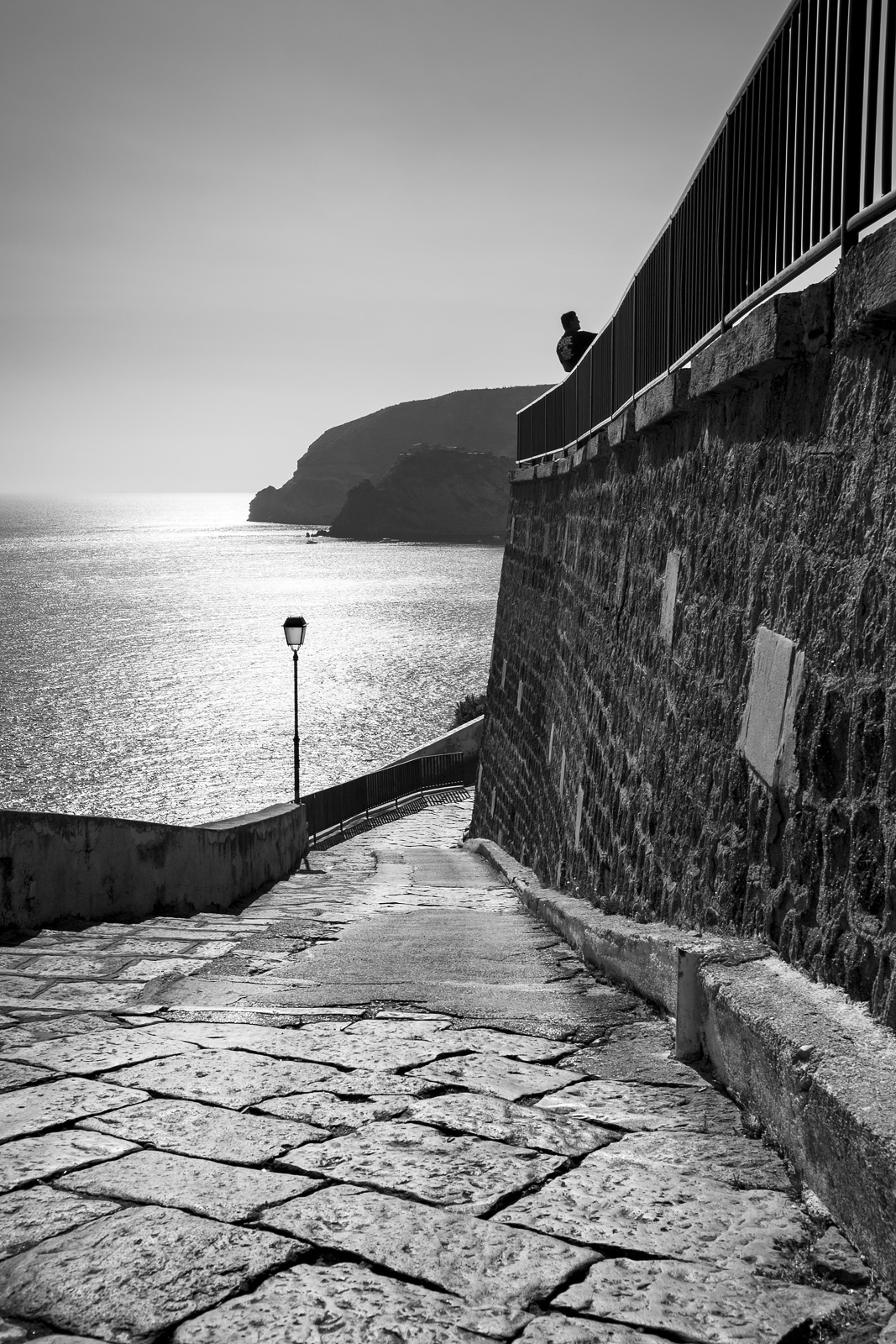 Man by railings above narrow flag stone street on hillside with street lamp silhouetted by sunlight reflected on sea in background Provinciale Succhivo Sant'Angelo, Sant'Angelo Italy black and white monochrome rustic street portrait composition © P. Maton 2018 eyeteeth.net