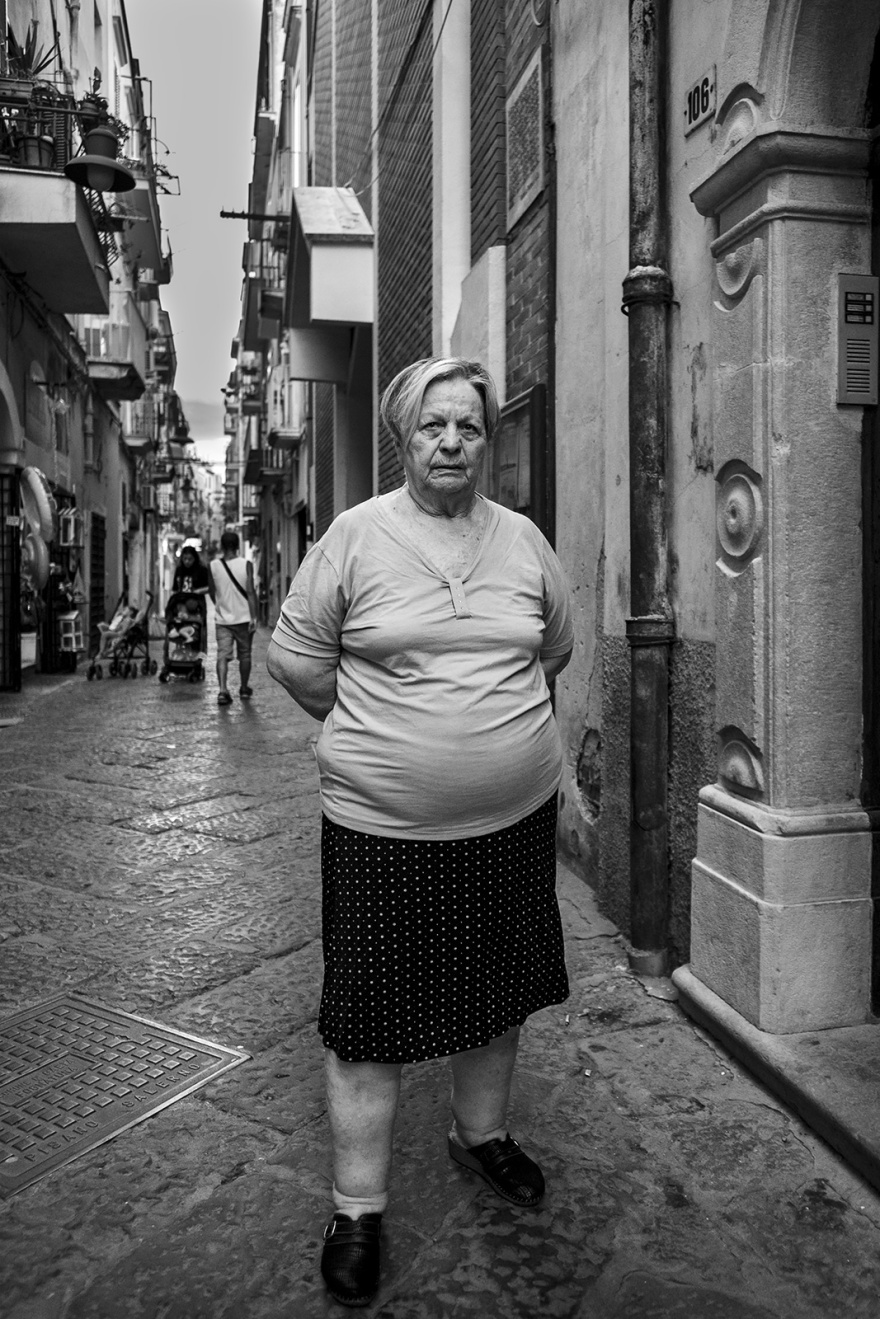 Local woman facing viewer standing in narrow street with flag stone floor Via dell'indipendenza  Gaeta  Italy  black and white monochrome street documentary portrait ©P. Maton 2018 eyeteeth.net